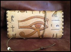 Made of genuine leather in natural color . The Hieroglyphs are burned with a pyrographer. Inside the pouch there are pockets for filters, rolling papers and lighter. It closes with a cord decorated with beads (It can be made with magnetic snaps as well)  Dimensions: 15cm x 24cm