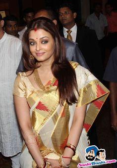 Aishwarya Rai in white cotton tradition sari with golden and pink temple border. Aishwarya Rai, named the most beautiful woman in the world. Kerala Saree, Indian Sarees, Silk Sarees, Kanjivaram Sarees, Mangalore, Bollywood Fashion, Bollywood Actress, Indian Dresses, Indian Outfits