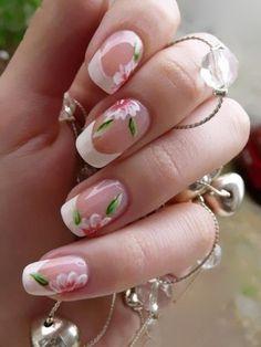 Fra i disegni più belli per una French Manicure originale vi sono questi fiori sulle tonalità del bianco, rosa e verde.