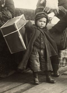 Picture Id: 603487	   An immigrant boy carries luggage at Ellis Island. Location:	Ellis Island, New York City, New York, USA. Photographer:	PAUL THOMPSON/National Geographic Stock See More Images by this Photographer