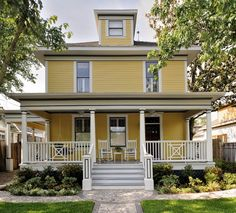 A porte cochere and criss-crossing balustrades add to the vintage charm of this classic American foursquare-style home