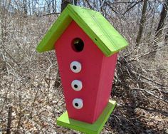 The entry hole is 1 1/4 in diameter, perfect size for songbirds.  7 long 6 1/2 wide 11 tall. The birdhouse has been painted violet red and has a lime green roof and base. The wire on top makes it easy to hang.  The bottom unscrews so you can clean it out. There are three white knobs that accent the front of the birdhouse.  This one has been made in the shape of a trapezoid.  A perfect birdhouse to add some color in your yard or garden.    Thanks for looking.