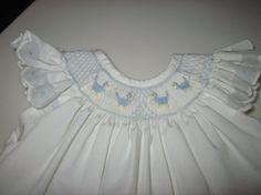 Vintage 1970s hand smocked baby dress. Hand made, hand smocked baby girl dress.  Dress is white cotton with blue smocking.
