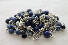 First Communion is around the corner!     This is a beautiful Catholic rosary perfect for a First Communion gift. It consists of 5 decades which each have 10 beads. The Ave beads are clear 6mm blue Sodalite. The Pater beads are 8mm blue Lapis.