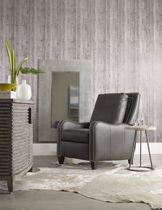 A modern take on a classic, the Greco Reclining Chair is upholstered in luxe leather and embellished with gleaming decorative nailheads that accentuate its streamlined silhouette in a manly way.