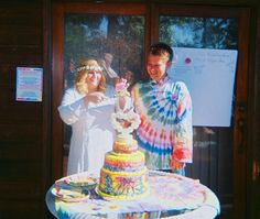 Just married hippies cutting the tie-dyed wedding cake