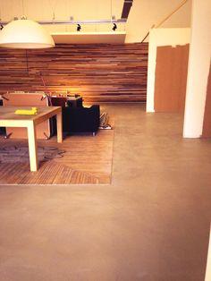 Houten wand van diverse latten en Beton-look vloer. Showroom Bizan Keukens Amsterdam