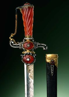 A ceremonial hunting dagger from the studio of Johann Melchior Dinglinger measuring 29 1/2 inches in length. It is made of partially gilded steel, silver, gold, carved carnelian and 330 diamonds with a leather sheath. Avid hunter that he was, Augustus the Strong had four ceremonial hunting daggers in his collection. Photograph by Jürgen Karpinski, courtesy of the Grünes Gewölbe, Staatliche Kunstsammlung Dresden.