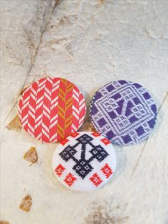 Kogin embroidered designs on button brooches.