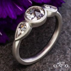 Platinum bezel set three stone ring with rose cut round .57ct and (2)rose cut pear shaped side stones totaling .39ctw.