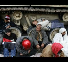 Egyptian anti-government demonstrators sit next to a military vehicle in Tahrir Square.