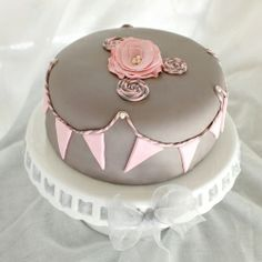 A soft grey and pink cake inspired by obsessions with bakers' twine, flag bunting, pearls, and fabric rosettes.