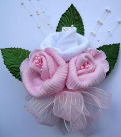 Baby sock corsage; Sweet idea but would be less cheesy using live baby's breath and greenery.