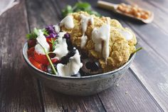 A vegetarian falafel bowl with loads of veggies! Low FODMAP falafel made with millet with bell pepper, olives, red cabbage lettuce and a tahini dressing.