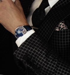 Timepiece:Van Cleef & Arpels Midnight Poetic Wish timepiece in white-gold case and dark blue alligator 'clair de lune' skin strap.  Style: Gucci Black and gray print single-breasted silk cotton two-piece suit and white cotton shirt; Mariano Rubinacci black print silk tie; Charvet black, white and red print pocket square; Alfred Dunhill platinum-plated tie bar.