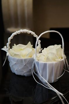 Baskets of white rose petals, decorated with ribbons and pearls, awaited the flower girls.