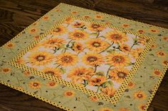 Handmade quilted sunflower table topper - ready to ship.  Cheerful sunflower table topper featuring yellow and gold flowers on a cream background with coordinating green border. The borders and binding are coordinating fabrics that complement the flowers perfectly. The backing fabric is the same as was used on the border, featuring smaller flowers on a light green background. Versatile enough for spring or fall, this table topper would bring a cheerful and striking splash of color to any…