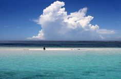 """'My Island, My Cloud, My Life' - photo by Daniela Hartmann (alles-schlumpf), via Flickr;  There is a boy sitting on a sandbank.  """"It looks [like] he is far away from civilization, but ... [he] is not far away from the beach.""""  Photographed in Kenya"""