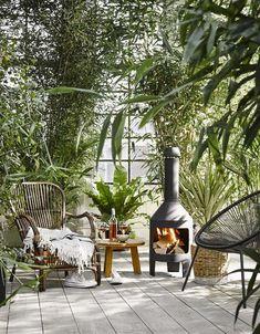 Refuge de douceur sur cette terrasse : fauteuil en rotin et mini cheminée d'extérieur - 12 idées déco pour la terrasse