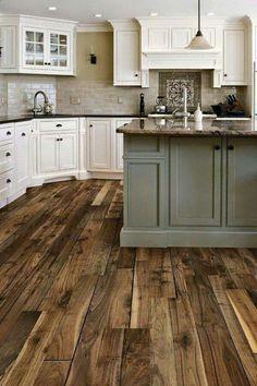 Kitchen. Dark wood floor. White and pale green cabinets. Dark counter tops. Cream backsplash.