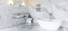 Torrco Design Center's Stamford location features several suites with various themes pertaining to each. Classic and clean vignette with all white fixtures, freestanding tub, polished nickel hardware and Calacatta stone are in the entrance of the showroom.