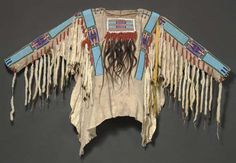 A CROW BEADED HIDE WAR SHIRT  painted overall with red dots, sewn with Crow stitch beadwork in pink, yellow, white, white heart red, two shades of green, and three shades of blue beads against a light blue beaded ground, trimmed with ermine fur streamers wrapped with red wool trade cloth, rectangular bibs on the front and back, with linear beadwork and hair pendants wrapped with red wool yarn; 60 in. (152.4 cm.) across the arms. belonged to Thunder Eyes (George Amos), Nez Perce medicine man