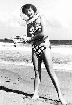 "Photographer and model, Bunny Yeager poses with a ""space"" helmet and ray-gun on a Miami Beach c.1952  ""Bunny Yeager""????"