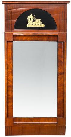 A MIRROR. Mahogany veneered, demi-lune shaped top with gilded mythological glass decoration. Russia, early 19th century. Height 147 cm, width 77 cm