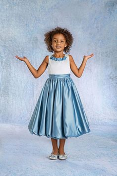 This beautiful satin flower girl dress has all the youthful appeal and elegance to be the winning look at your next special event. The sleeveless satin dress features a bodice with a rosette trimmed neckline and full gathered balloon hem skirt meant to fall at tea length. Both youthful and elegant, this dress has everything you need to make a lasting impression for that special occasion.
