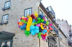 Colorful plastic objects seemingly explode out of buildings in public art by José Luis Torres.