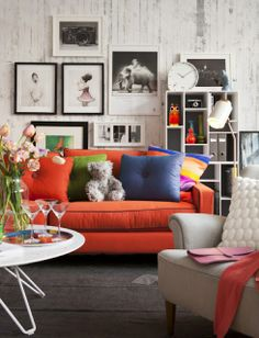 Interior living room - frames, couch, books, bricks wall - white & beautiful orange colors.