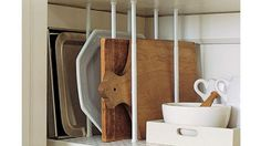 Tension curtain rods are used inside a cabinet or cupboard to divide cutting boards, platters, trays, baking sheets, etc.