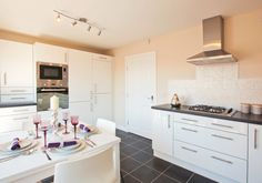 Dunelm Homes - Blyth.  Bang on the money kitchen design, it's beautiful, it's sleek, white, contemporary, it won't date.  I love the white gloss dining table with the shaded purple/mauve glassware. not sure about the weird tiling above the hob - I'd have put a purple glass splashback and a lovely green lush plant to the left.