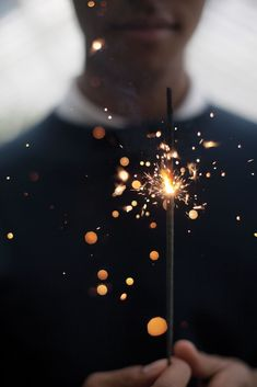 To get a photo like this, you would get someone to have a sparkler in their hands that is lit, while you take a photo of the sparks up close. you would want to have your shutter speed quicker so that you could get the individual little sparks and not just one big blur of a light.