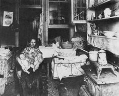 "An unknown photographer captured this New York mother and her two babies in an old-law tenement apartment in 1916.  Like most flats in old-law tenements (so named because they predate ""new"" turn-of-the-century laws mandating better living conditions per apartment), it's dark, squalid, and unventilated.  That window probably looks out onto a narrow courtyard, if not just another room in the same apartment."