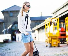 Pernille Teisbaek wears a white pussy bow blouse with denim cutoffs, mirrored sunglasses, and a Chanel bag