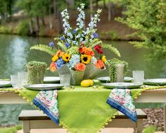 Spanning shades of blue and green, a vivid palette for this waterside setting echoes the natural surrounds, while stunning blooms bring a rainbow of color reflected in the linens and dinnerware.    #southernladymag #tabletopinspo #outdoorentertaining #diningalfresco #prettyflowers #tablescapes #summerinthesouth #summerentertaining #summertabletops Southern Ladies, Centerpieces, Table Decorations, Outdoor Entertaining, Pretty Flowers, Shades Of Blue, Tablescapes, Floral Design, Table Settings