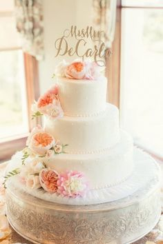 This romantic three tiered white wedding cake was topped with a wrap of fresh peach roses and blush peonies. Kinda perfect, right?! Pics: Figlewicz Photography http://www.confettidaydreams.com/peach-pink-palos-verdes-wedding/