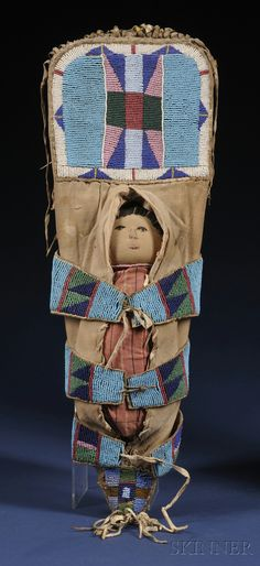Plains Model Cradle, Crow, c. late 19th century, the wood form with muslin cover & decorated with classic Crow beadwork on hide, fringed at the top & bottom, includes a cloth doll, ht. 19 in.