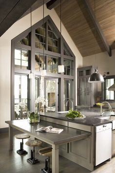 The open kitchen features an earthy palette of muted grays and browns, natural accents, warm wooden tones, but sophisticated finishes like stainless steel appliances and marble style counter tops. French doors open to screened porch with stone fireplace.