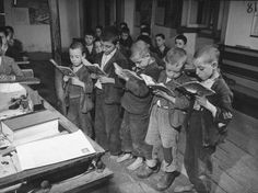 Little boys reading their paperback books in the classroom.  Location:	Portugal  Date taken:	1940  Photographer:	Bernard Hoffman