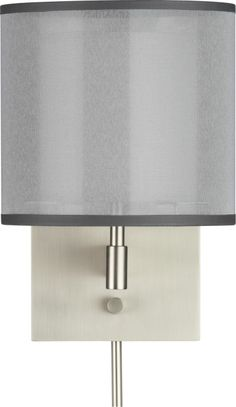 "Eclipse Silver Wall Sconce | Crate and Barrel 8"" dia. x 11.75""H Stainless steel - Brushed nickel finish Polyester exterior shade, cotton-poly blend interior shade 60W max. - Accommodates compact fluorescent lightbulb (not included) On/off switch Translucent cord and two 12"" cord covers Plug in or direct wire Made in China Overall Dimensions - Height: 11.75"" Diameter: 8"" Backplate - Width: 6"" Depth: 0.75"" Height: 8"" Shade - Height: 5.5"" Diameter: 8"