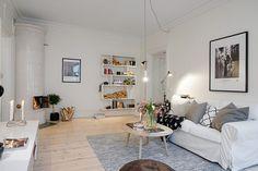 Skandynawski styl w pokoju dziennym - jasna drewniana podłoga, żarówka na kablu w minimalistycznym stylu, biała sofa ozdobiona poduchami, czarny pled, szary dywan i brązowa pufa.Minimalizm został tu wyniesiony na piedestał, a le to w nim właśnie tkwi tajemnica skandynawskich wnętrz. Mniej znaczy więcej.