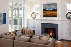 """As popular as open floorplans are today, they pose a challenge to designers trying to create a feeling of warmth and shelter within a large, flowing space. Designer Tineke Triggs shares her process for this cozy family room: """"Proper layout was key in the design and the use of the space,"""" she says. """"Layering rich colors and textures adds warmth while the large, bold print on the carpet ties all the elements together, creating a comfortable and cohesive space."""" Of course, the fireplace…"""