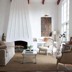 Thirties-style living room with white walls and open fireplace