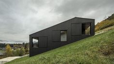 The asymmetrical roof follows the gradient of the slope, enhancing the sense that the house might slide down the hill at any moment. The austere black timber cladding is relieved by large cut-outs and windows.