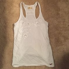 Detailed Hollister Tank Top White Hollister Tank Top with sequins and details on the front. Floral design. Super cute, and soft.  Same / Next day shipping, always!  Hollister Tops Tank Tops