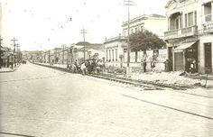 """1930 - Rua da Liberdade vista em direção sul. À direita, cartaz com propaganda do filme """"O Rei do Jazz"""", no Cine Rosário da rua de São Bento."""