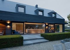 House in the Netherlands upgraded with a dark grey cladding of timber panels and tiles.