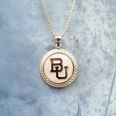 Gold and white BU Baylor Bears pendant. (Via @universityjewelery on Instagram)